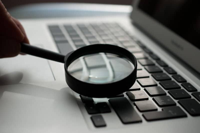 holding a magnifying glass up to a laptop