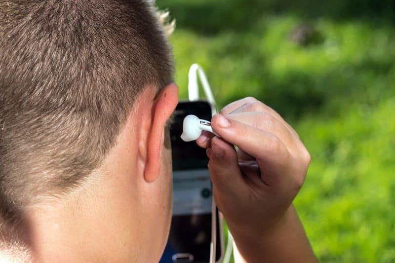 musicinan inserting an earplug