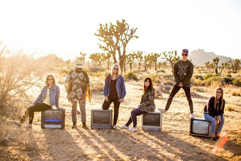 band photo taken in a desert with crt televisions