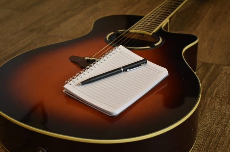 acoustic guitar with a notebook