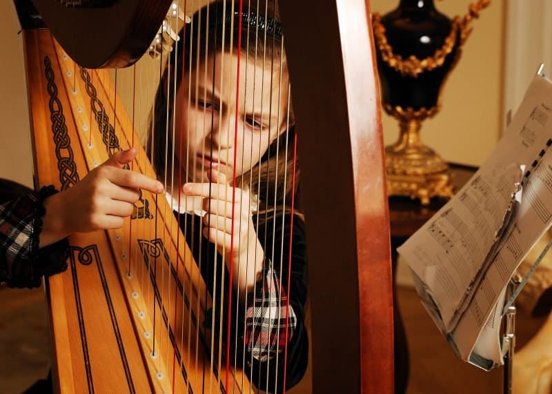 kid playing a harp