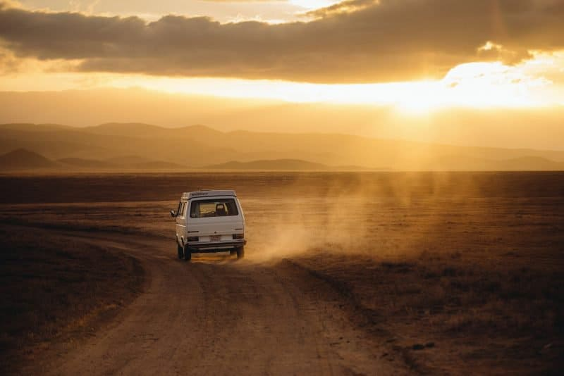 single van driving in a desert, symbolizing a solo artist on their own