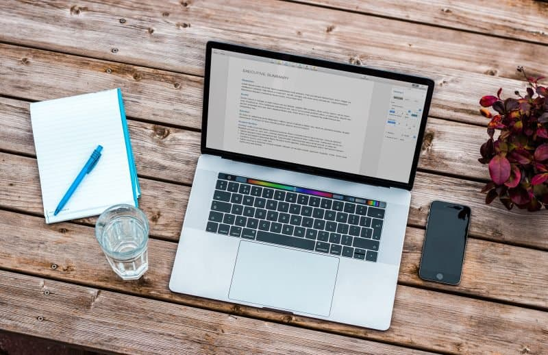 macbook and notepad to plan an electronic press kit