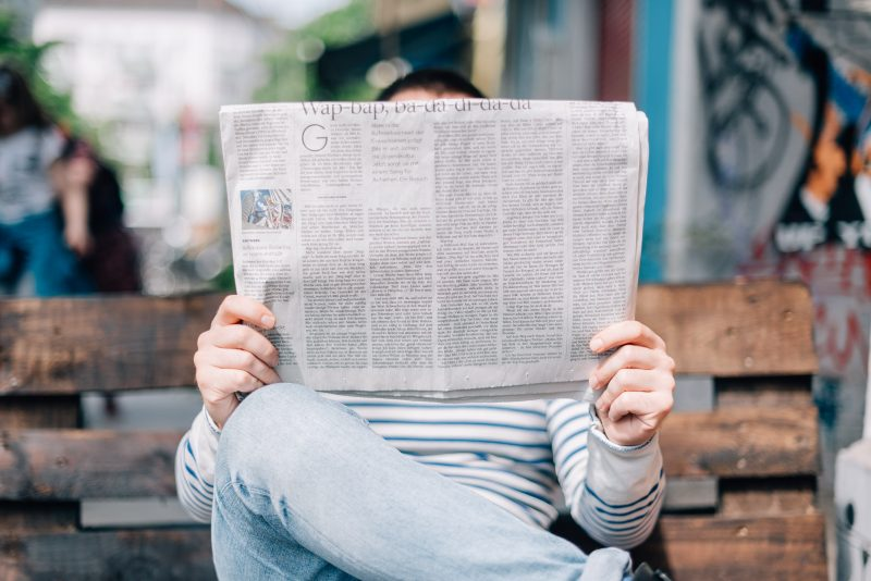 person looking at a newspaper