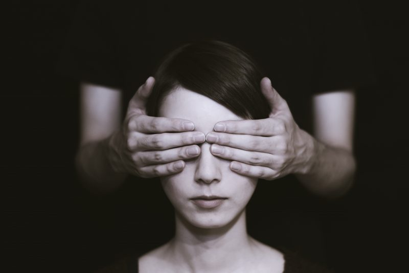 person with their eyes covered to symbolize mixing without a reference track