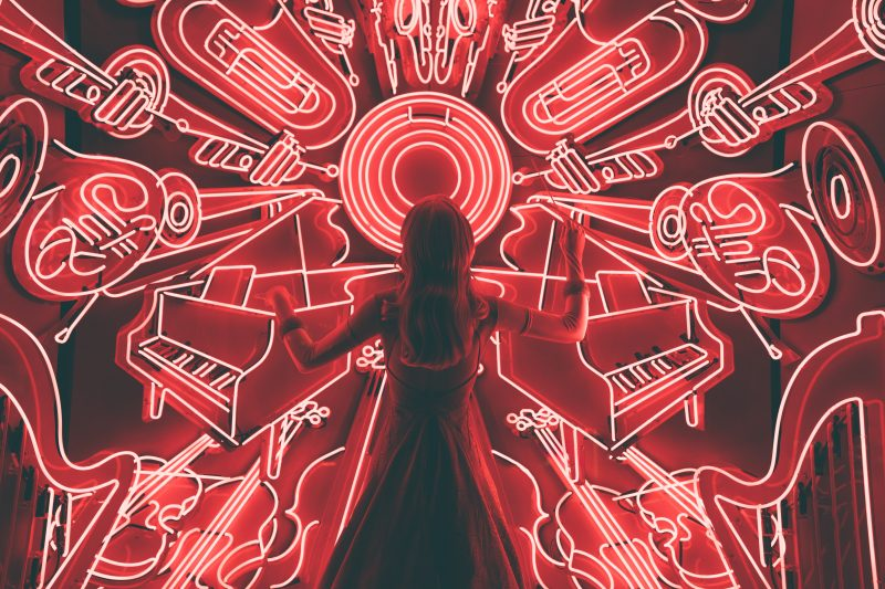 musician conducting a neon light orchestra