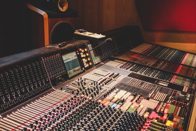 analog mixing console with faders, knobs, and outboard mixing gear