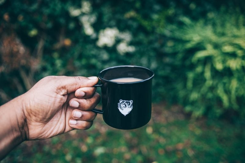 person holding a custom mug of coffee with a bear logo on it