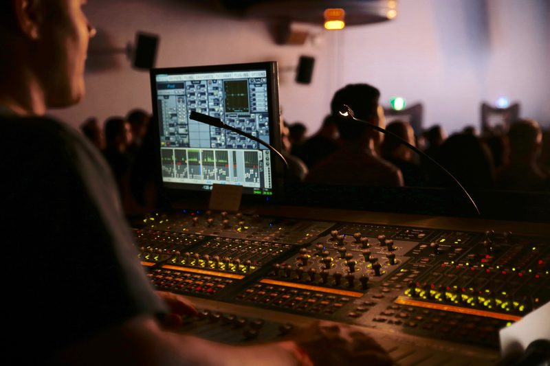 live audio engineer behind a mixing desk