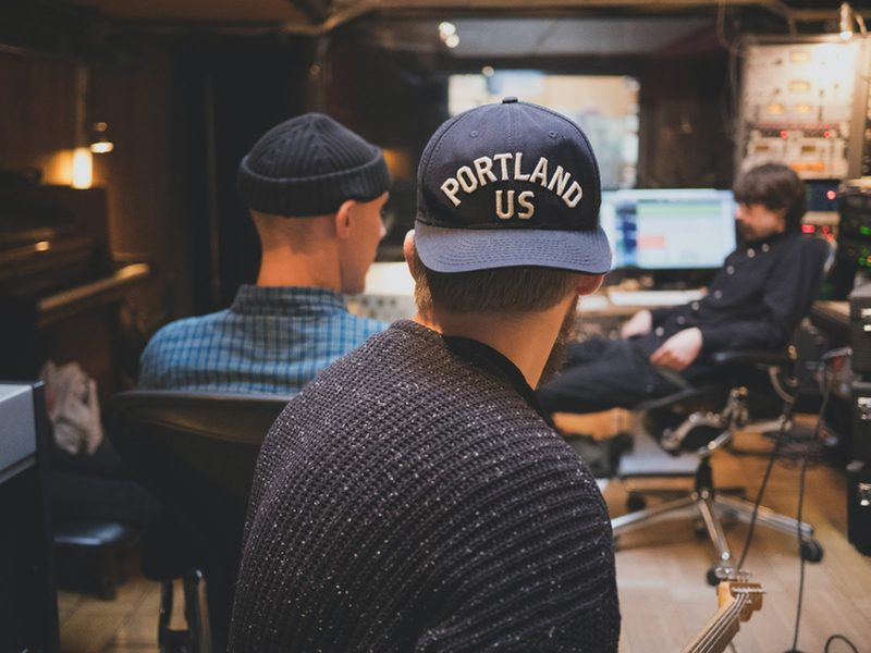 two musicians watching an audio engineer work in a tracking studio