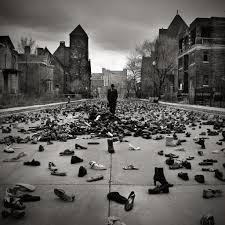 black and white songwriting prompt image of a person standing in a town square, surrounded by shoes