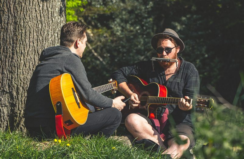 two musicians playing guitars outside