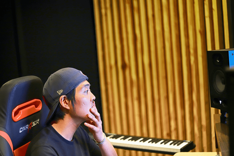musician sitting in a studio next to a keyboard